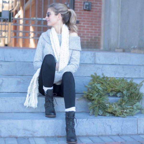 grå tröja med en axel med svarta leggings och snörstövlar