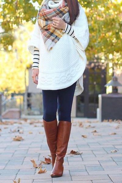 vit tunikatröja med vida ärmar och knähöga stövlar i brunt läder