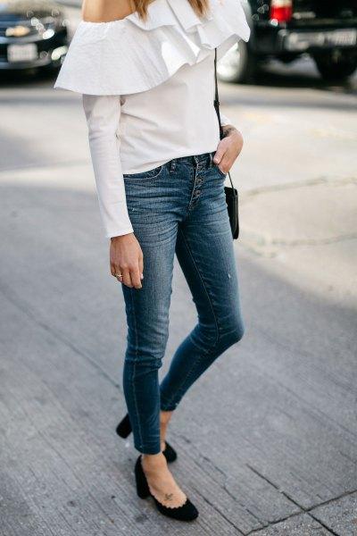 vit axelblus med volanger och jeans med knappfickor