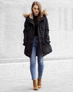 svart bomberjacka med huva gjord i fuskpäls och smal passande blå jeans