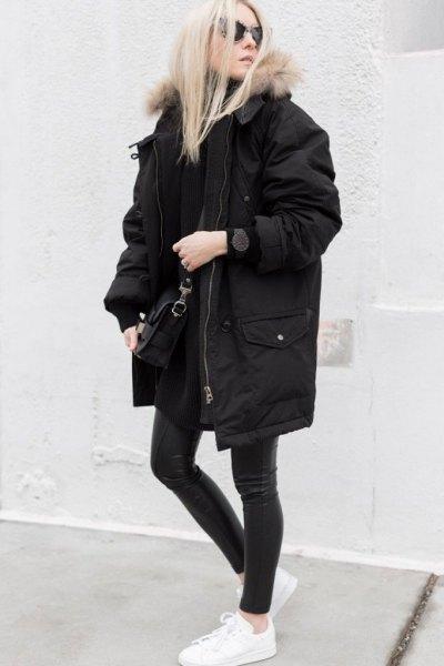 lång oversized svart vinterrock med mörkgrå skinny jeans och vita sneakers