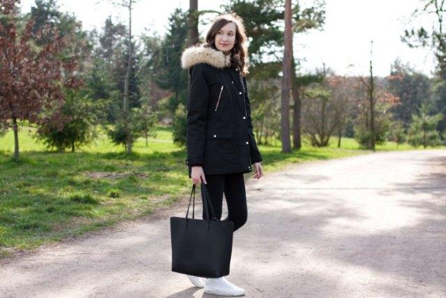 svart lång kappa med huva i fuskpäls med matchande jeans och sneakers