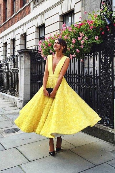 gul midiklänning med spetspassning och flare med djup V-ringning och svarta klackar