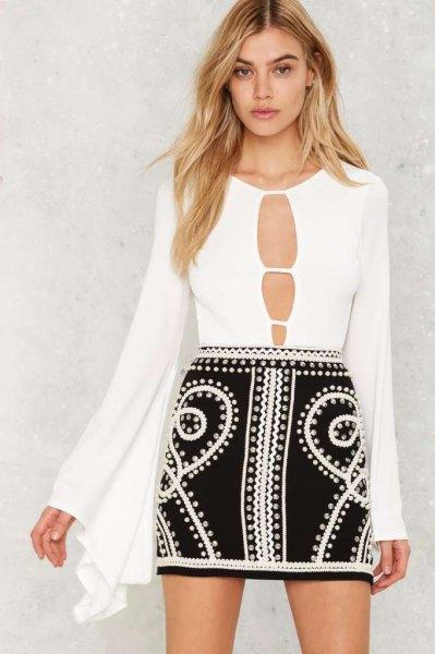 vit bodysuitblus med klockärmar fram och svart minikjol