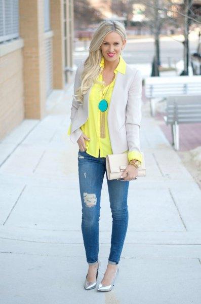 gul skjorta med knappar, ljusgrå kavaj och smala jeans