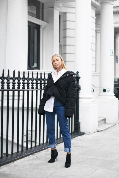 vit skjorta med knappar, svart överdimensionerad vinterjacka och jeans med muddar