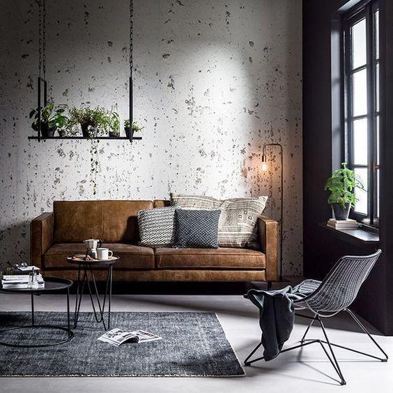 Modernt skandinaviskt industriellt vardagsrum med en brun sammet.