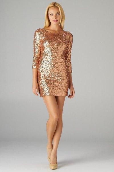 långärmad guldklänning med paljetter och figurklädda rosa klackar