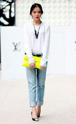 vit långärmad T-shirt med ljusblå jeans med manschetter och gul koppling