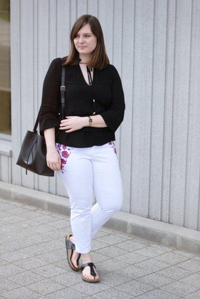 svart blus med V-ringning och ljusblå broderad slim fit-jeans