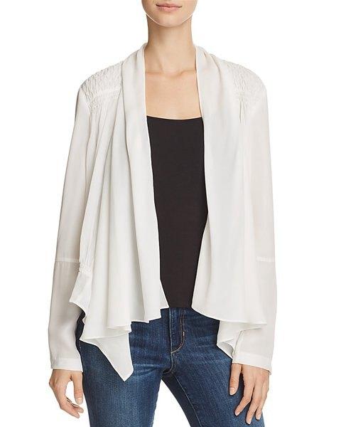 vit sidenjacka med svart västtopp och blå skinny jeans