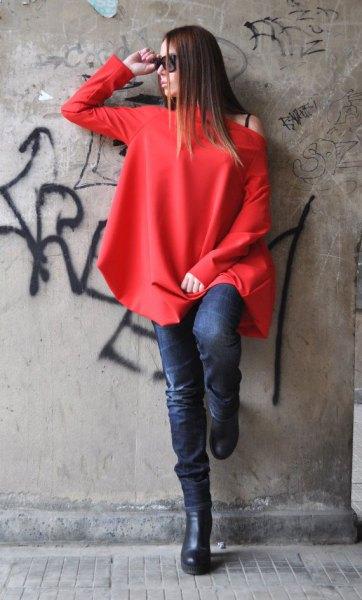 röd långärmad topp med en axel och mörkblå skinny jeans