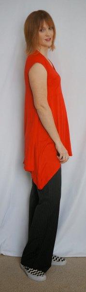 asymmetrisk ärmlös tunika med svarta byxor med vida ben
