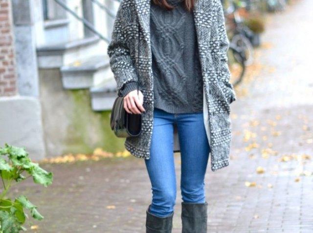 grå lång tröja med ljusblå jeans och svarta knähöga stövlar