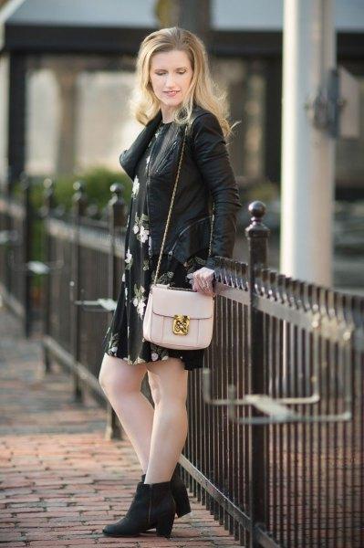 Läderjacka med svart miniklänning med blommig gunga och stövlar med klackar