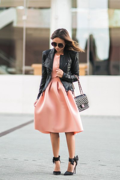 svart skinnjacka med rodnande rosa passform och utsvängd midiklänning