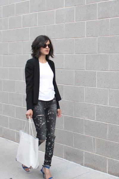 svart kavaj med vit T-shirt och blålackade jeans med muddar