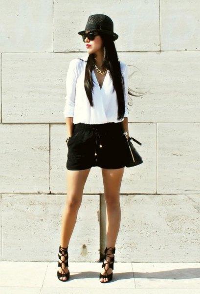 vit wrap-blus med svart kort kort hatt och platt hatt