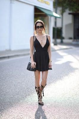 svart cocktailklänning med djup V-ringning och flare med knähöga sandaler