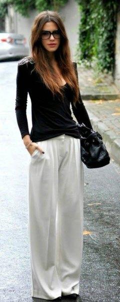 svart figur-kramad tröja med scoop halsringning och vita byxor