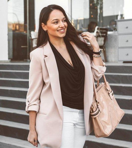 Ljusgrå khaki-kavaj med svart blus med kåpan och vita jeans