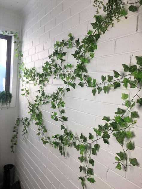 Avkopplande trädgård med mycket murgröna som växer upp väggarna 2020.