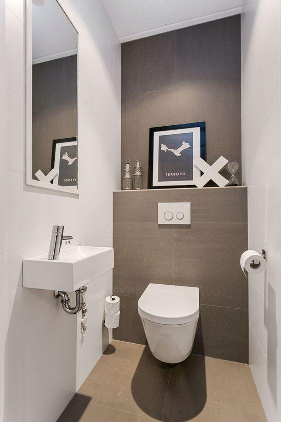 en neutral gästtoalett gjord i taupe och vitt, ett konstverk, en vägg.