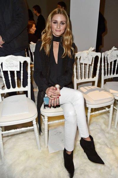 svart blus med djup V-ringning, vita skinny jeans och fotkängor