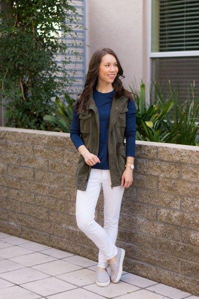 brun bruksväst med mörkblå långärmad topp och vita jeans