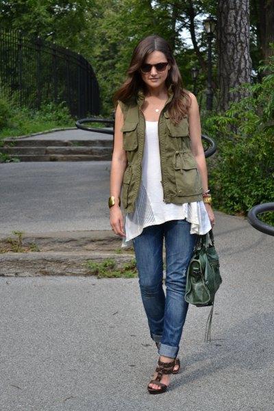 grön bruksväst med vit ärmlös tunikatopp och blå jeans med muddar