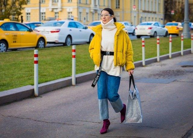 gul jacka med svart turtleneck och vida jeans