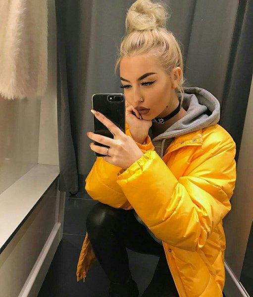 gul jacka med grå huvtröja och svarta skinny jeans