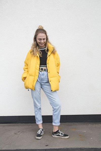 gul pufferjacka med svart, kort tröja och mom jeans