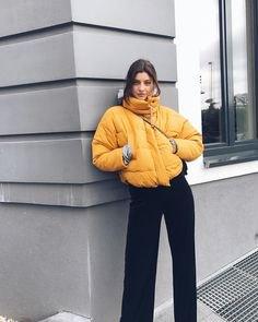 gul pufferjacka med svarta jeans med vida ben