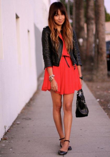orange miniklänning med svart skinnjacka och läderremmar med ankelband