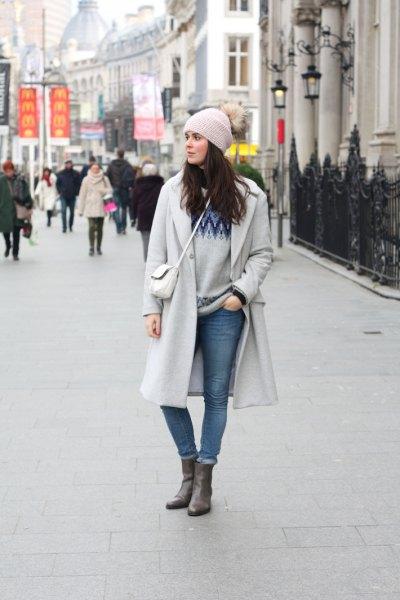 grå stickad mössa och matchande lång vinterrock och midjebandsjeans