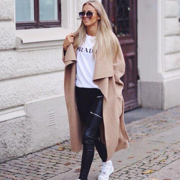Vinterrock i kamel taxilängd med vit tryckt T-shirt och svarta läderbyxor