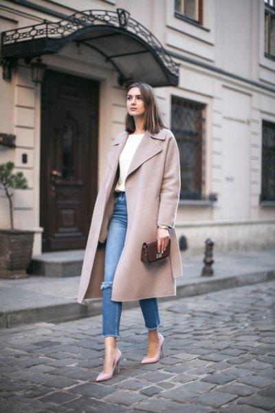 grå vinterullrock med lång linje och blå smala jeans