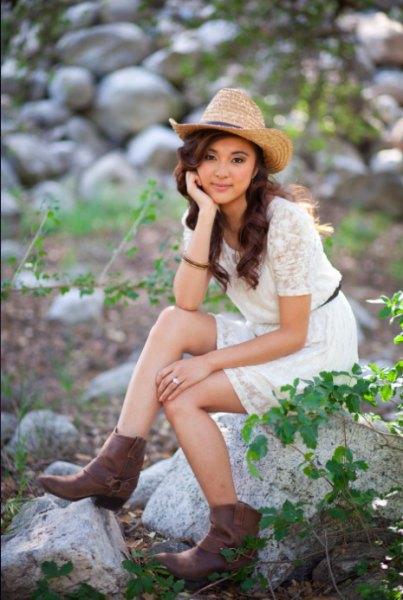 Halm cowboyhatt med en vit mini spets klänning med korta ärmar och bälte
