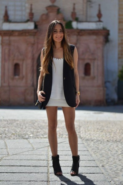 vit miniklänning med scoop-halsringning och svart ärmlös lång jacka