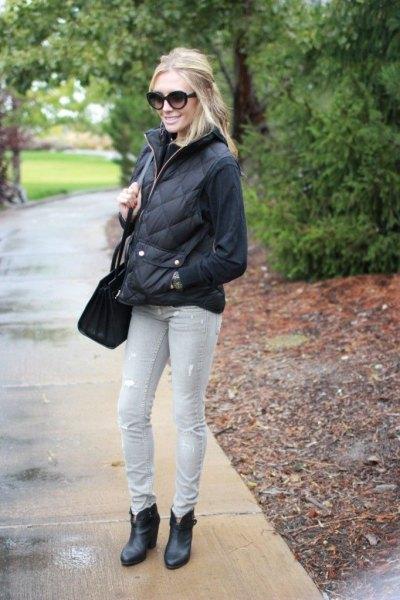 svart tröja med quiltad pufferjacka och ljusgrå jeans