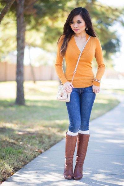 Skräddarsydd tröja med senap och V-ringning, blå jeans och grå knähöga stövlar