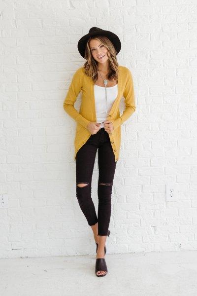 gul kofta med vit linne med en urringning och rippade skinny jeans