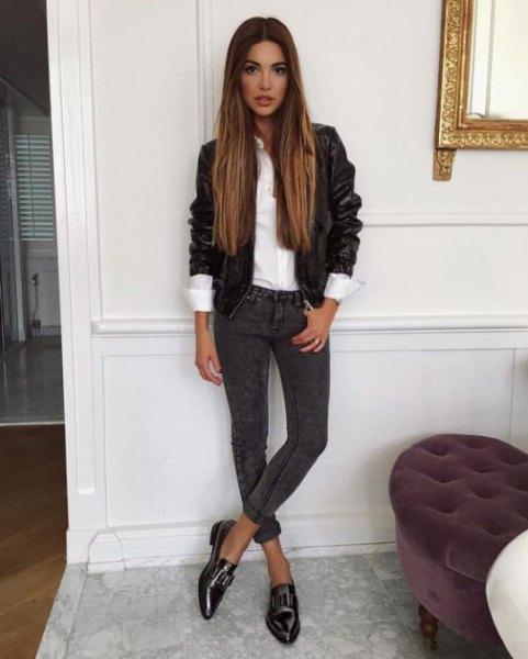 svart skinnjacka med vit skjorta och mörkgrå skinny jeans med manschetter