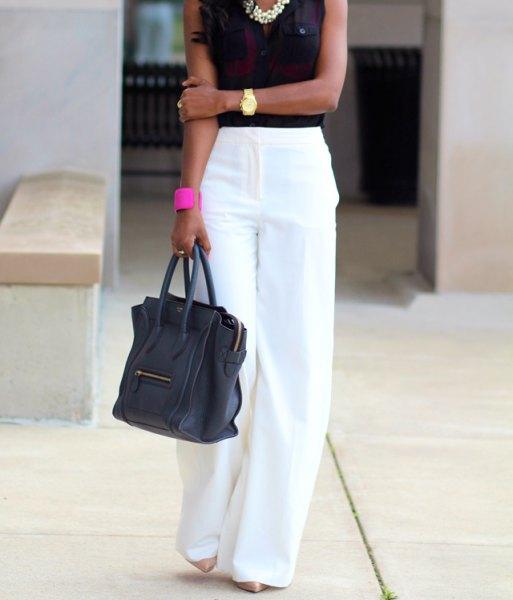 vita byxor med svart ärmlös blus och uttalandekedja