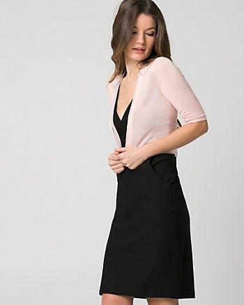 vit bolerojacka med halva ärmar, svart slida klänning med djup V-ringning