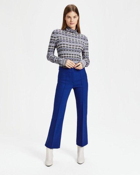 svart tryckt tröja med mock hals och blå byxor