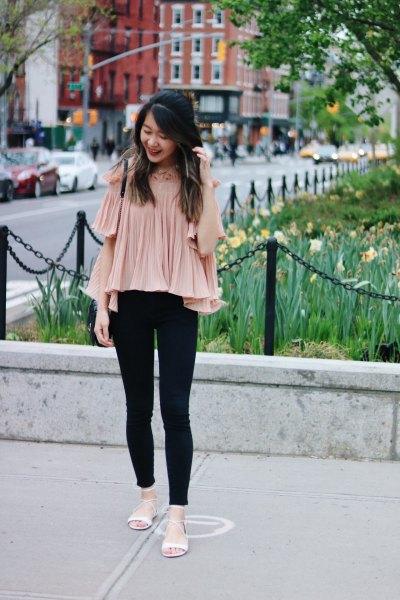 ljusrosa veckad chiffongblus med kall axel och svarta jeans