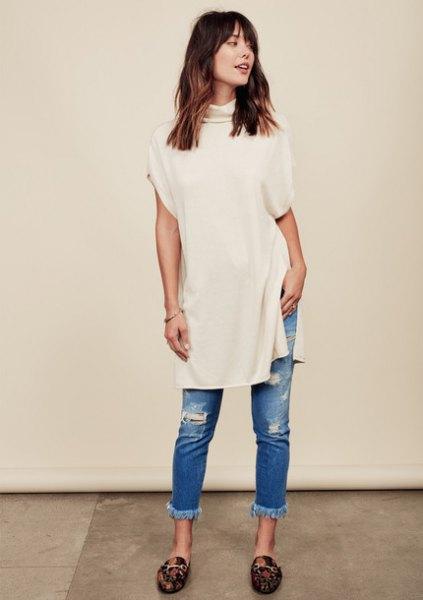 Ljusrosa tröja i mock-hals med rippade jeans med muddar