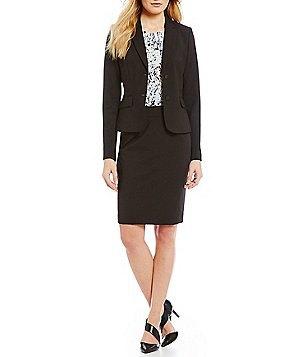 svart kostym består av en kort kappa och penna kjol